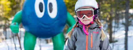 Flicka i alpinutrustning med Bärra Blåbär i bakgrunden