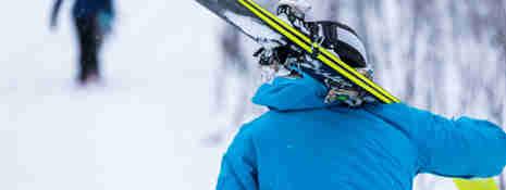 Slalomåkare som går med slalomskidor på axeln