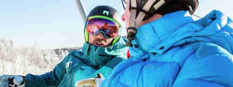Skidlärare samtalar med en vuxen elev i sittlift