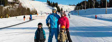Familj på slalomskidor som står tillsammans nedanför en alpinbacke