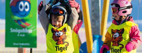 Glada barn i slalomhjälm som står framför en liftkarusell