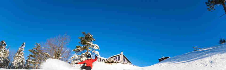 Snowboardåkare som åker ned för alpinbacke i solen
